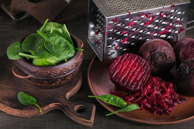 Sałatka z buraków gotowanych na ciemnej drewnianej powierzchni, gotowane buraki i liście szpinaku w glinianej misce
