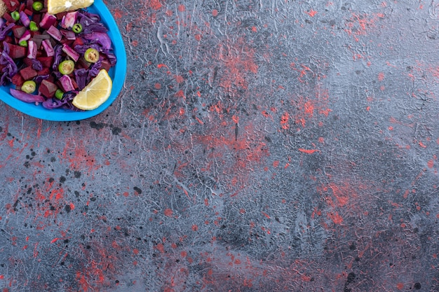Sałatka z buraków i czerwonej kapusty na talerzu przyozdobionym plasterkami cytryny na czarnym stole.