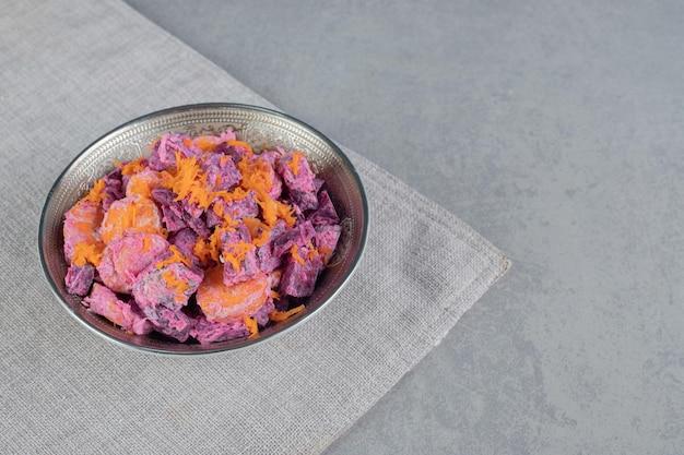 Sałatka z buraków i marchwi fioletowy na desce.