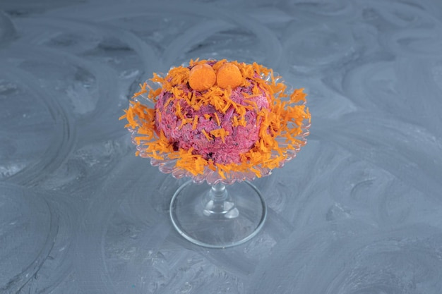 Sałatka z buraków i orzechów włoskich przyozdobiona marchewką i podana na szklanym cokole na marmurowej powierzchni.