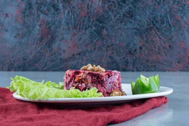 Sałatka z buraków, marchwi i kalafiora. przyozdobionym orzechami włoskimi, ogórkami i liśćmi sałaty na marmurze.