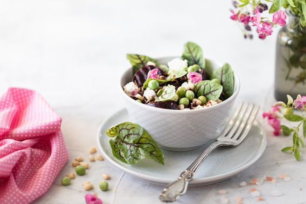Sałatka z buraków, sera, zielonego groszku i orzeszków piniowych. sałatka wegetariańska z warzywami i świeżymi liśćmi chard.
