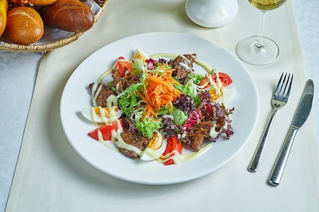 Sałatka z ciepłym kurczakiem, pomidorami, sałatą, jajkiem i marchewką na białym talerzu. obsługa restauracji pyszne przekąski
