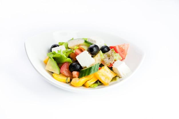 Sałatka z czarnymi oliwkami, ogórkiem i serem na białym tle