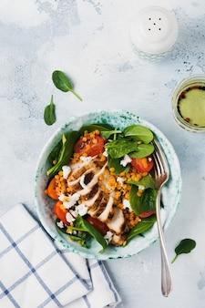 Sałatka z czerwoną soczewicą, liśćmi szpinaku, pomidorkami koktajlowymi, mięsem z kurczaka i serem mozzarella z oliwą z oliwek w płycie ceramicznej na starym betonowym szarym tle.