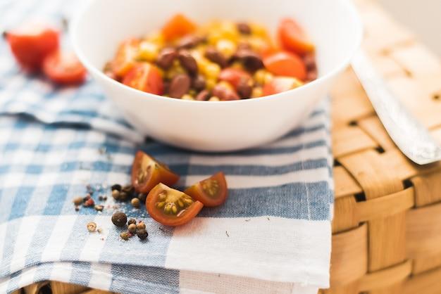 Sałatka z czerwonej fasoli, żółtej kukurydzy, krakersów. kosz piknikowy i piękny niebieski ręcznik.