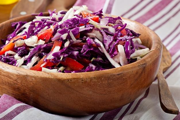 Sałatka z czerwonej i białej kapusty i słodkiej czerwonej papryki, doprawiona sokiem z cytryny i oliwą z oliwek w drewnianej misce
