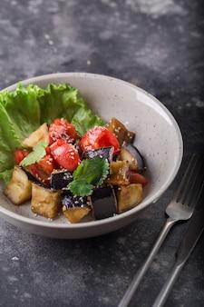 Sałatka z duszonego bakłażana i pomidora z sałatą i sezamem na białym talerzu.