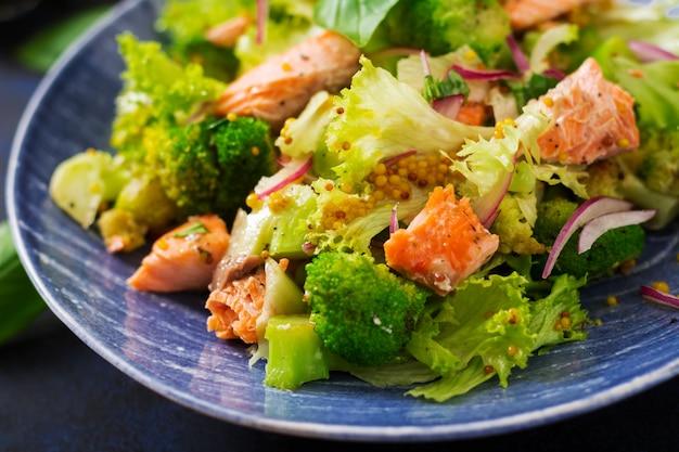Sałatka z duszonym rybim łososiem, brokułami, sałatą i dressingiem. menu rybne. menu dietetyczne. owoce morza - łosoś.