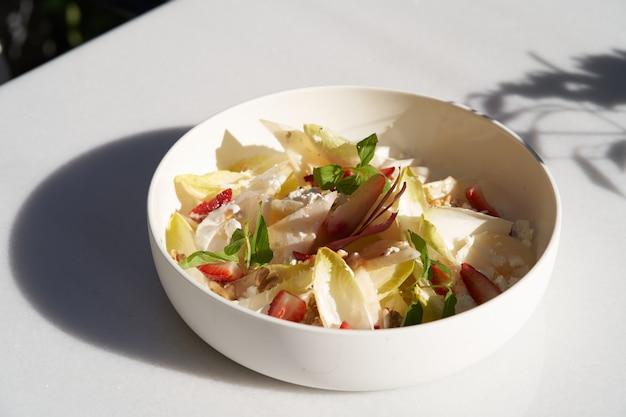 Sałatka z endywii z kozim serem, truskawkami i orzechami włoskimi. sałatka z liści cykorii belgijskiej na stole