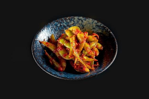 Sałatka z fasoli edamame w pikantnym czerwonym sosie podana w ciemnej misce