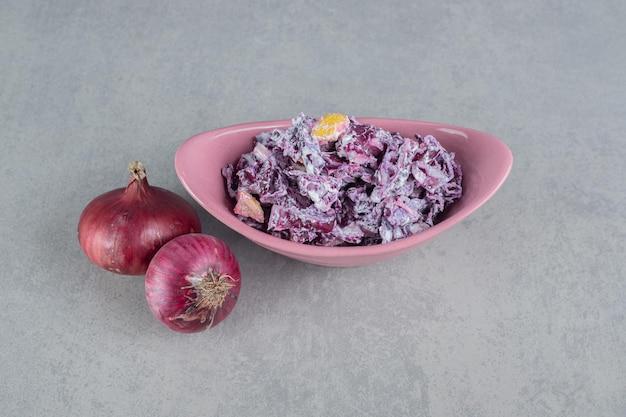 Sałatka z fioletowej kapusty i cebuli w ceramicznym kubku.