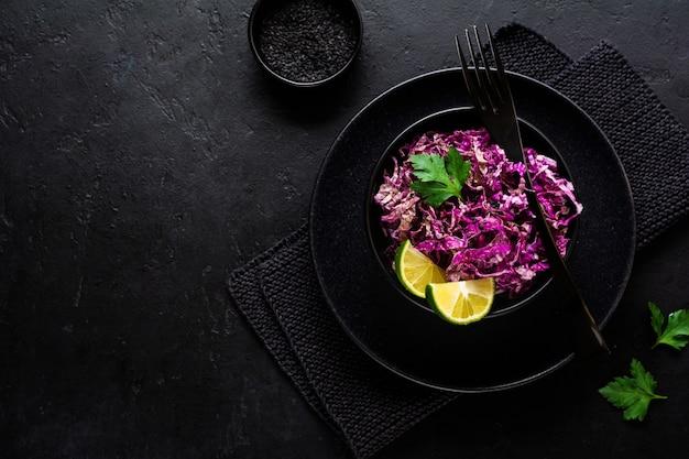 Sałatka z fioletowej kapusty pekińskiej z oliwą z oliwek, limonką i czarnym sezamem w płycie ceramicznej na ciemnej betonowej powierzchni.