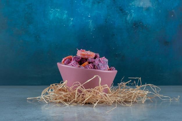Sałatka z fioletowymi burakami i marchewką w ceramicznym kubku.