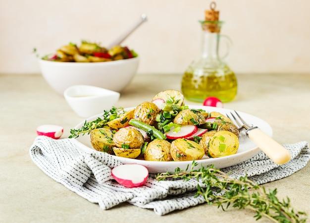 Sałatka z gorących ziemniaków z zieloną fasolką, rzodkiewką i dressingiem ziołowym z oliwą z oliwek i sosem musztardowym.