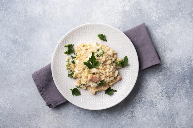 Sałatka z gotowanego ryżu, czerwonej ryby różowy łosoś jaja i warzywa na talerzu. skopiuj miejsce