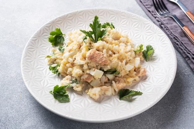 Sałatka z gotowanego ryżu, czerwonej ryby różowy łosoś jaja i warzywa na talerzu.