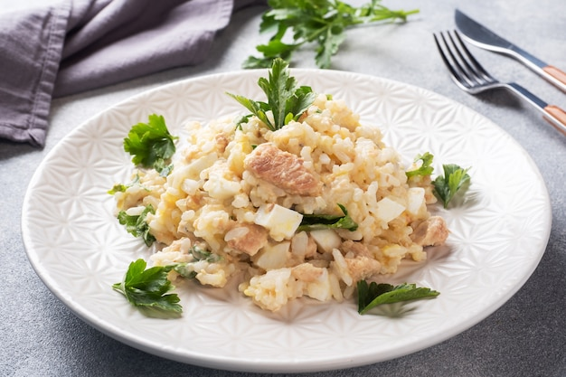 Sałatka z gotowanego ryżu, ryb, jajek i zieleni na talerzu