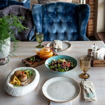 Sałatka z gotowanego szpinaku i czosnku na niebieskim talerzu cytryna i imbir na grillowanym talerzu