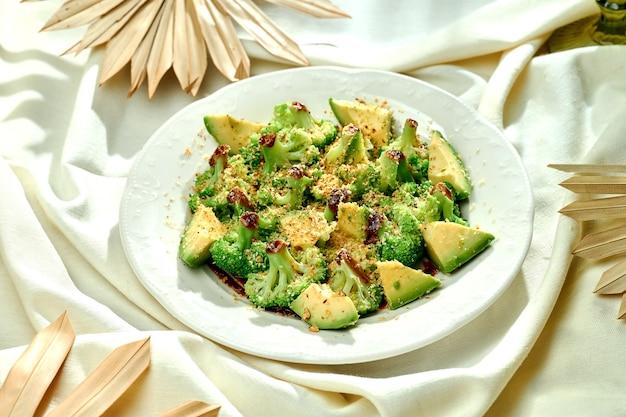 Sałatka z gotowanymi brokułami z orzechami i sosem balsamicznym w białym talerzu na obrusie