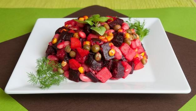 Sałatka z gotowanymi warzywami. flakonik na sole trzeźwiące. podstawowym składnikiem winegret jest burak. jedzenie wegetariańskie.