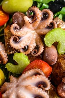 Sałatka z grillowaną ośmiornicą, ziemniakami, rukolą, pomidorami i oliwkami. czarne tło. widok z góry