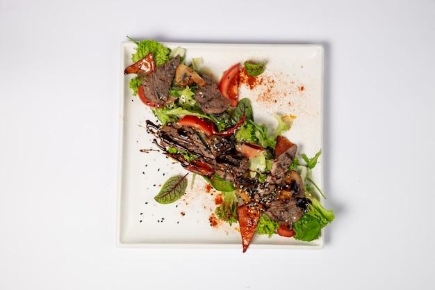 Sałatka z grillowaną wołowiną prime z grillowanymi warzywami na poduszce z mixem sałat i sosem miodowo-musztardowym. na białej powierzchni