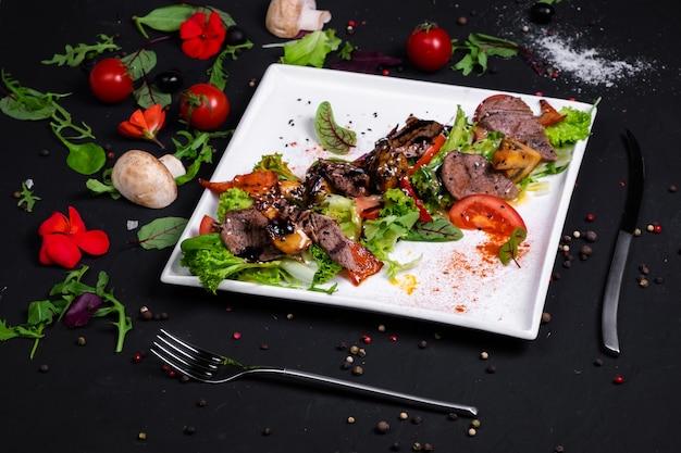 Sałatka z grillowaną wołowiną prime z grillowanymi warzywami na poduszce z mixem sałat i sosem miodowo-musztardowym. na ciemnej powierzchni