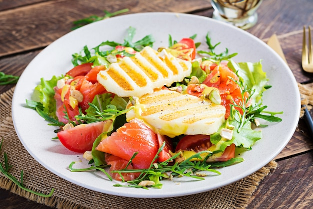 Sałatka z grillowanym serem halloumi z solonym łososiem, pomidorami i zielonymi ziołami. zdrowa żywność na talerzu na drewnianym tle.