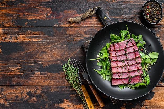 Sałatka z grillowanym stek z tuńczyka teriyaki z rukolą i szpinakiem. ciemne drewniane tło. widok z góry. skopiuj miejsce.