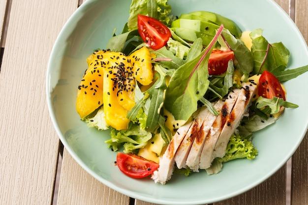 Sałatka z grilowanym kurczakiem, mango, sałatą, awokado, pomidorami, rukolą, suserem serowym na białym talerzu