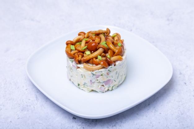 Sałatka z grzybami (grzyb miodowy), szynką, ziemniakami, serem i majonezem. tradycyjna rosyjska sałatka «kosz z łyka grzybowego». selektywna ostrość, zbliżenie.