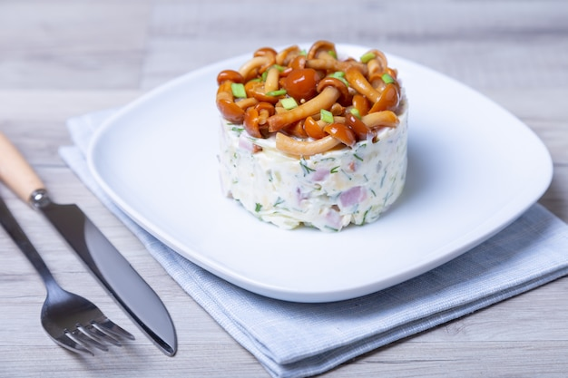 Sałatka z grzybami (miodem), szynką, ziemniakami, serem i majonezem. tradycyjny rosyjski sałatkowy kosz na pieczarki. selektywne ustawianie ostrości, zbliżenie.
