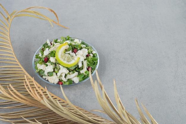 Sałatka z kalafiora na talerzu z pestkami granatu i ziołami.