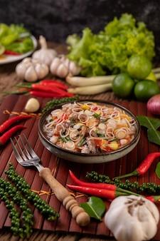 Sałatka z kalmarów z kolendrą, posiekaną zieloną cebulą, czosnkiem i kukurydzą na talerzu