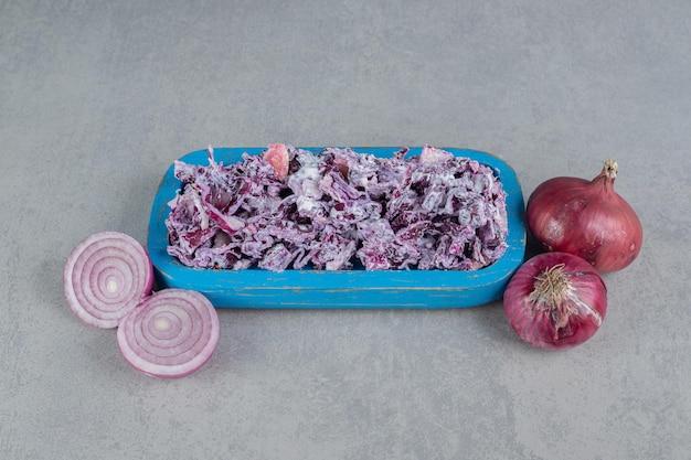 Sałatka z kapusty fioletowej i cebuli na półmisku.