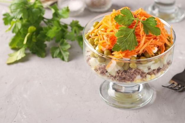 Sałatka z koreańską marchewką, mięsem i groszkiem w puszkach w przezroczystych salaterkach szarej powierzchni, kopia przestrzeń