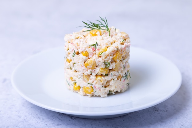 Sałatka z kraba z kukurydzą i jajkami na białym talerzu. tradycyjna sałatka rosyjska. zbliżenie.