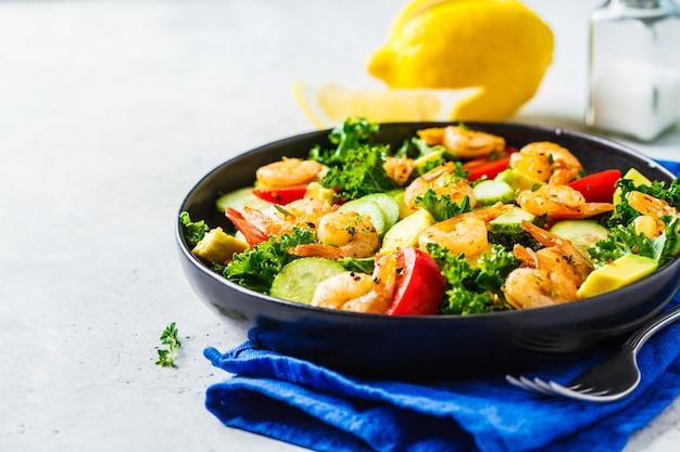 Sałatka z krewetek, awokado i warzyw w czarnym naczyniu na szarym tle.