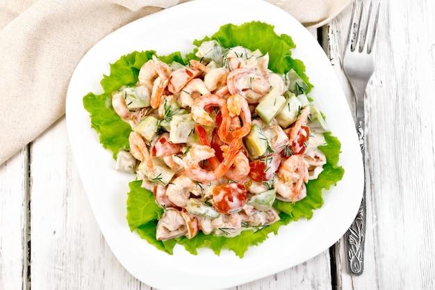 Sałatka z krewetkami, awokado, pomidorami i majonezem na zielonej sałacie na talerzu, serwetka, widelec na tle drewnianych desek na wierzchu