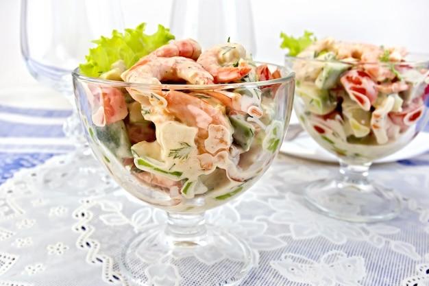 Sałatka z krewetkami, awokado, pomidorem i majonezem, zielona sałata w szklanym kielichu na serwetce, talerz na tle niebieskiego lnianego obrusu