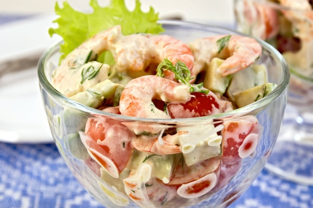 Sałatka z krewetkami, awokado, pomidorem i majonezem, zielona sałata w szklanym kielichu, talerz na tle niebieskiego lnianego obrusu