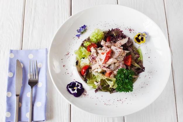 Sałatka z kurczaka i grzybów na białym talerzu, ozdobiona kwiatami