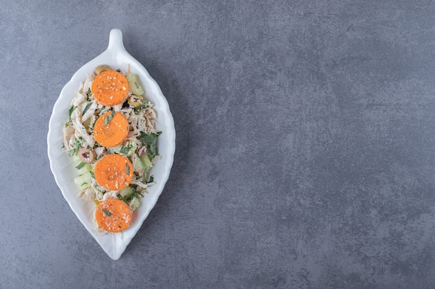 Sałatka z kurczaka pokrojona w kostkę na talerzu w kształcie liścia.