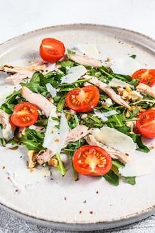 Sałatka z kurczakiem, rukolą, orzechami włoskimi, pomidorami i parmezanem. szara powierzchnia. widok z góry