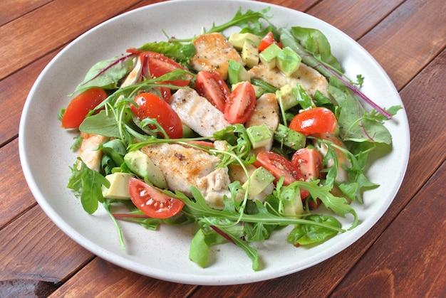 Sałatka z kurczakiem z awokado i pomidorami koktajlowymi, rukolą i liśćmi buraków. zdrowy lunchu puchar z warzywami i kurczakiem na drewnianym tle. koncepcja zdrowej żywności