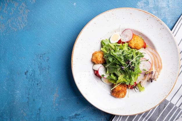 Sałatka z kurczakiem z chrupiącymi kulkami, sałatą i warzywami. widok z góry.