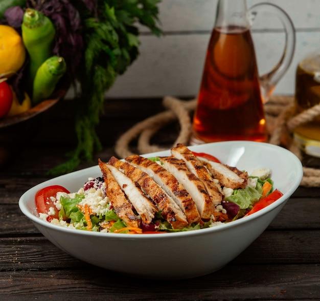 Sałatka z kurczakiem z warzywami i twarogiem na stole