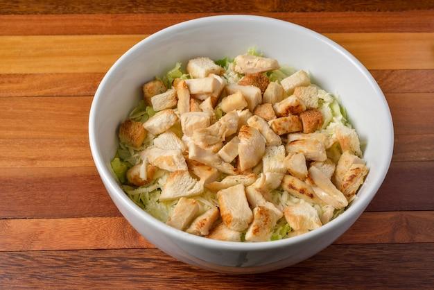 Sałatka z kurczakiem z warzywami w białej misce.