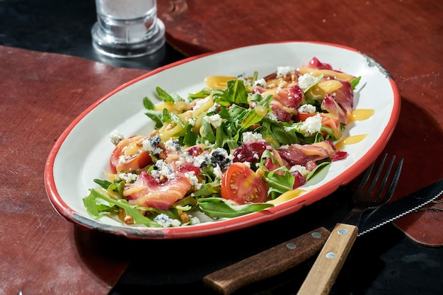 Sałatka z lekko solonym łososiem, serem dorblu, pomidorkami koktajlowymi i żółtym sosem w białym talerzu. ciemna powierzchnia. ostre światło